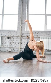 Graceful girl while doing ballet positions. Woman is stretching before dance.