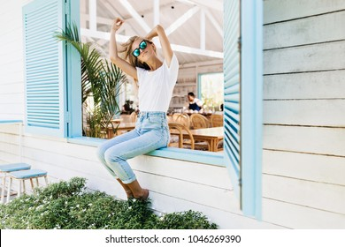 Graceful happy girl sitting on window sill and playing with her blonde hair. Photo of positive caucasian slim lady in jeans enjoying photoshoot in summer day.