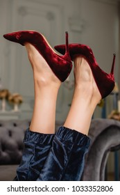 graceful legs of the girl in red velvet high-heeled shoes in the living room gray-blue