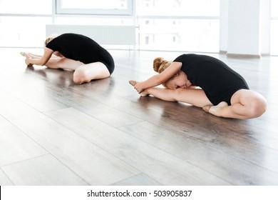 Graceful little ballerina and her teacher stretching legs in ballet studio