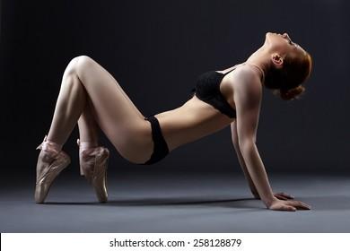 Graceful modern ballet dancer posing at camera