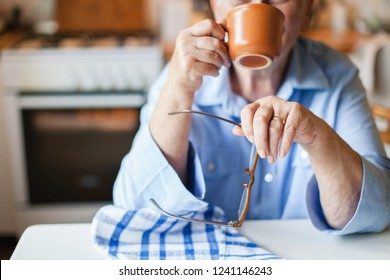Graceful old hands. Senior woman is drinking hot beverage from mug in cozy home kitchen. Retired person is sitting and holding cup of coffee and spectacles. Grandmother with wedding ring has tea break