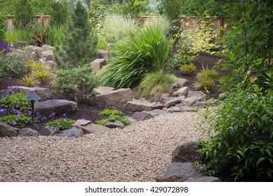 A graceful pebbled walkway winds through this   perennial backyard garden.