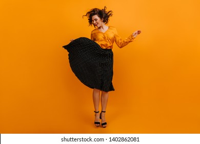 Graceful short-haired girl jumping on yellow background. Studio shot of charming woman in black skirt.