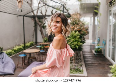 Graceful short-haired girl looking over shoulder in cozy street restaurant. Outdoor shot of pleasant tanned lady dancing in pink dress.