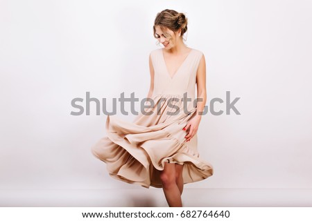 a7df8decf621 Graceful smiling girl with bun hairstyle posing while dancing on white  background. Amazing curly young