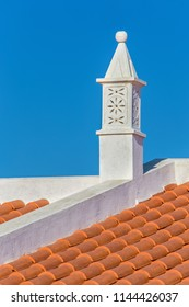 Graceful white chimney on roof with orange tiles
