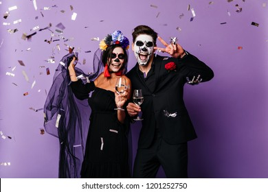 Graceful woman in colorful wreath celebrating halloween with boyfriend. Couple of vampires drinking champagne.