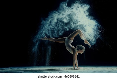 Graceful woman dancing in cloud of dust