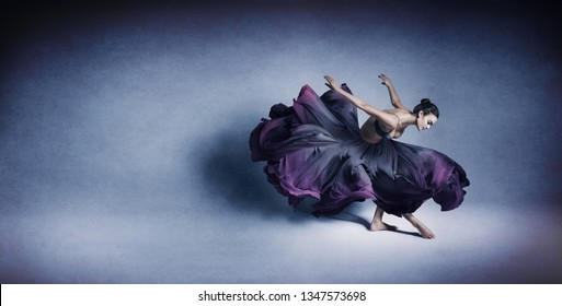 Graceful woman dancing in flowing dark blue dress like flower