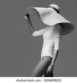 A graceful woman posing with a large wide-brimmed hat. Black and white image. - Shutterstock ID 1826898032