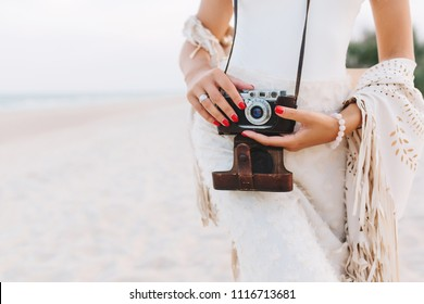 Graceful woman with red manicure and stylish ring holding camera on blur nature background. Outdoor portrait of tanned female photographer in white attire posing on sandy beach before photoshoot.