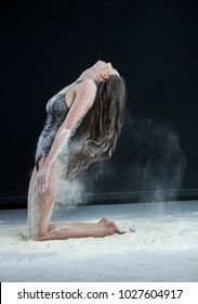 Graceful young beautiful sexy brunette with long hair dancing in cloud of dust.