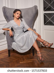 Graceful young lady wearing elegant silver glitter cocktail dress and high heels sitting and leaning on elegant armchair. Gorgeous brunette woman in classy outfit posing in luxurious apartment.