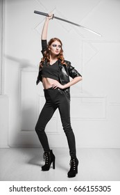 Graceful young model in black clothes posing with steel sword