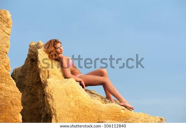 Graceful young woman in bikini lying on the yellow rock