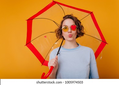 Graceful young woman in blue shirt posing with kissing face expression. Studio shot of pretty female model with curly hair fooling around during photoshoot with umbrella.
