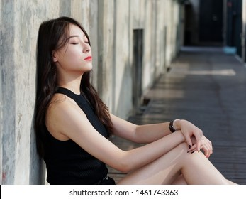 Graceful young woman with long black hair sitting on ground and leaning on the wall in suuny day. Outdoor portrait of cool Chinese girl in trendy summer sexy black dress and sandal, summer concept.