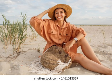 Graceful young  woman in trendy summer linen dress and straw hat posing on the beach near ocean. Bali style. Boho bag.