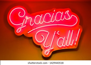 Gracias Y'all closeup of orange red neon sign in store shop for business on window