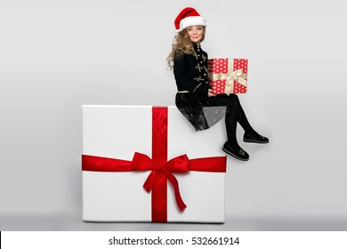 Gracious little girl with blond curly hair and smartly dressed in a red Santa Claus hat, sitting on a huge package with a red bow
