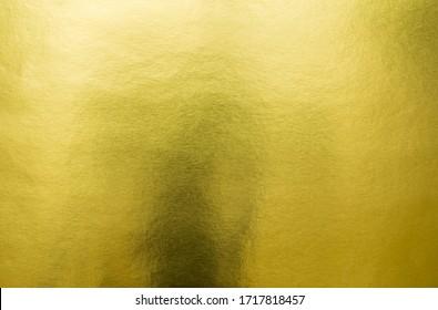 Gradation feuille de feuille de feuille dorée brillante sur fond jaune brillant texture métallique. Papier abstrait brillant doré pour modèle.  vue de dessus.