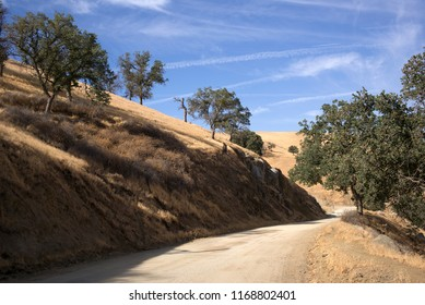 A graded dirt road meanders through the foothills of the Sierra Nevada Range flanked by black oak trees and dried grass.