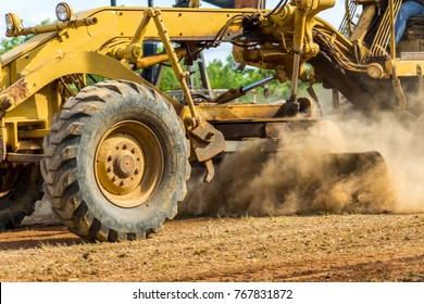 Grader clearing and leveling construction site surface. Grader industrial machine on construction work.