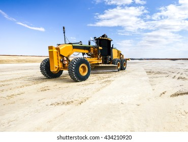 a  grader is a construction machine with a long blade used to create a flat surface during the grading process.