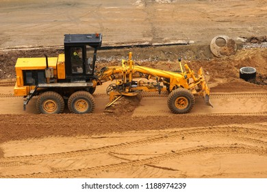 Grader leveled the ground on the construction of the road.