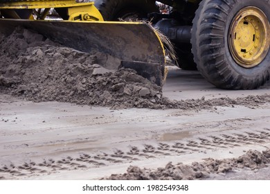 The grader levels the sandy road. Road construction works