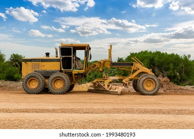 Grader Road Construction Grader industrial machine on construction of new roads. the blade of a motor grader in the process of leveling a sandy road foundation. Grader is working on road construction.