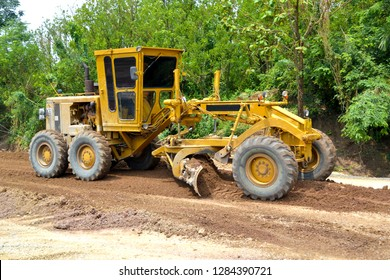 grader working on the road.grading on the road.motor grader is working on the road.front of the motor grader is working.grader industrial machine on construction of new road.