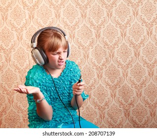 Gradeschool girl at home listening to music on a pair of vintage 1970s wired headphones reacts to the old style jack