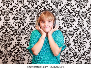 Gradeschool girl at home listening to music on a pair of vintage 1970s wired headphones