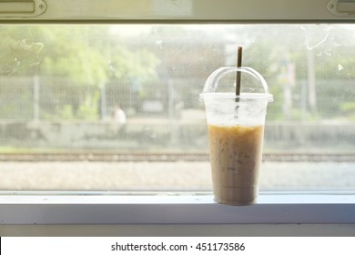 Gradient effect, glass of ice milk coffee on the window frame on the train in Thailand.