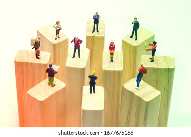 Gradient pastel color of miniature toys standing on wooden block - social distancing, anti-social or team work concept.