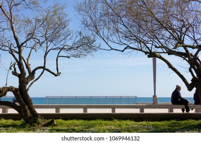 GRADO, Italy - April 13, 2018: Seafront promenade with a man seated on a bench