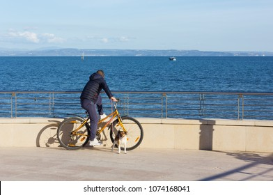 GRADO, Italy - April 13, 2018: A man on his bicycle on the seafront watching the sea with his dog on the leash