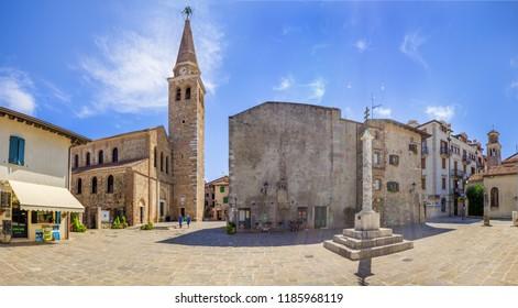 GRADO, ITALY - AUGUST 16, 2018: Historical center of famous north-eastern Italian city. Central area with Basilica of Sant'Eufemia on the left side. Province Gorizia. Region Friuli-Venezia Giulia.