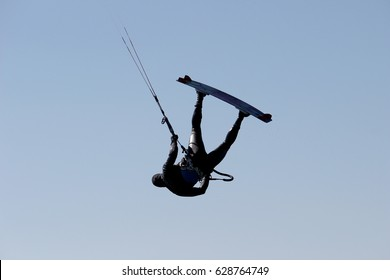 Grado, Italy - March 8, 2015: Kite Surfer silhouette. Jump high in the sky. On the photo only the Kite surfer high in the sky, without the sea. Photography was taken in Grado Beach, Italy.