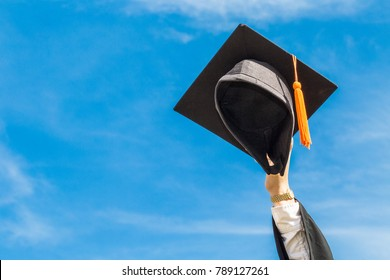 Graduate celebrating put graduation cap up to the sky feeling so proud and happiness in Commencement day,Education Success Concept