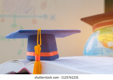 Graduate or Education knowledge learning study abroad concept : Graduation cap on opening textbook with blur of america earth world globe model map in Library room of campus, Back to School