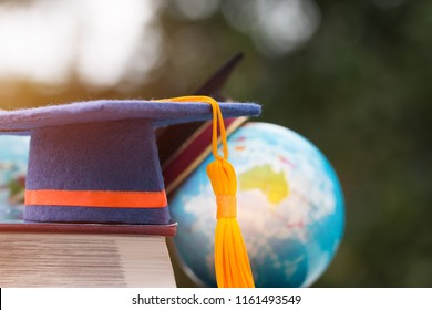 Graduate or Education knowledge learning study abroad concept : Graduation cap on book,  blur of australia earth world globe model map with light green background at outside in campus, Back to School