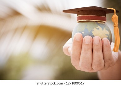 Graduate or Education knowledge learning study international abroad concept : Graduation cap on opening textbook with blur earth world globe model map in outdoor of campus, Back to School
