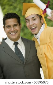 Graduate hoisting diploma with arm around father outside, portrait