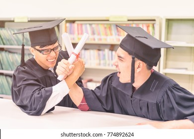 graduate students holding their diploma and arm wrestle