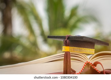 Graduate study abroad international college Ideas : Black graduation cap on old book at outdoor. Education is knowledge for learning and success in your life, Back to School ideas