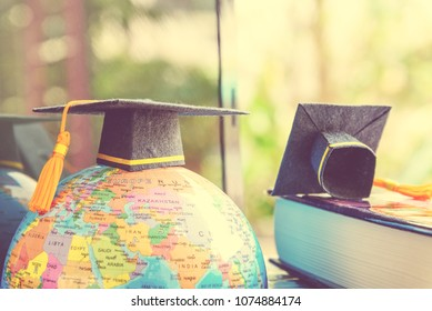Graduate study abroad program concept : Black graduation cap on a globe map and books, depicts knowledge can be learned online anywhere and everywhere, even in universities or campus around the world.
