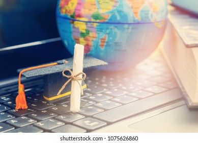 Graduate study abroad program concept : Diploma, graduation cap, a globe map and books, depicts knowledge can be learned online anywhere and everywhere, even in universities or campus around the world